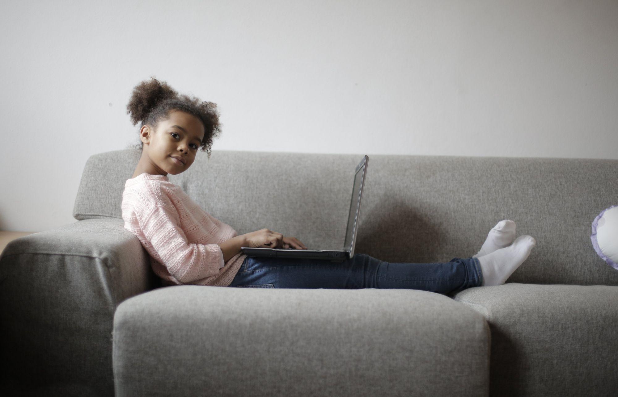 Petite fille aux cheveux frisés assise sur un canapé avec un ordinateur portable sur les genoux pour illustrer la facilité de partager des choses en ligne sur Internet