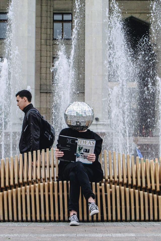 """Homme assis sur un banc publique tenant un journal à la main dont le titre est """"Ideas"""" (idées en Français). L'homme a la tête en forme de boule à facette."""